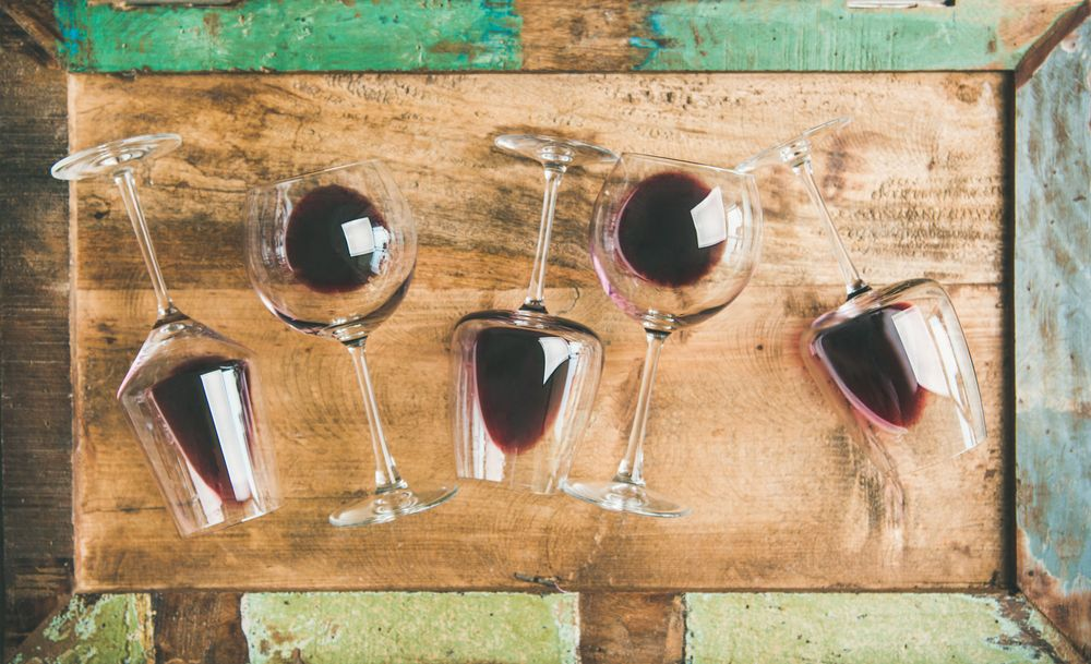 Flat-lay of red wine in glasses over rustic wooden tray background, top view. Wine bar, winery, wine tasting concept